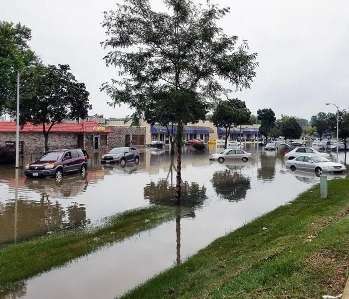 flooding in street and parking lot with cars and businesses in background